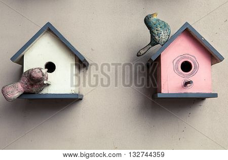 Two cute little birdhouses on wooden fence