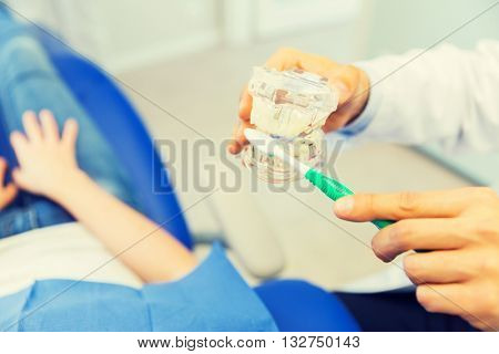 people, medicine, stomatology and health care concept - happy male dentist showing jaw and teeth layout to patient girl at dental clinic office