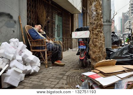 SHANGHAI CHINA - MARCH 18: Unidentified man rest in a street on March 18 2016 in Shanghai China. Shanghai is the largest Chinese city by population.