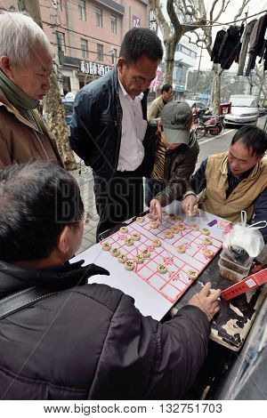 SHANGHAI CHINA - MARCH 18: Unidentified people play Chinese Chess in a street on March 18 2016 in Shanghai China. Xiangqi also called Chinese Chess is one of the most popular board games in China