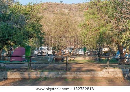 MOUNTAIN ZEBRA NATIONAL PARK SOUTH AFRICA - FEBRUARY 18 2016: Tents vehicles and people at the camping grounds in the Mountain Zebra National Park near Cradock at sunset