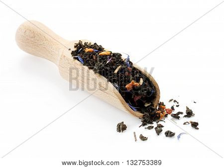 Black tea with slices of dried fruits and flower petals in a wooden scoop isolated on white background