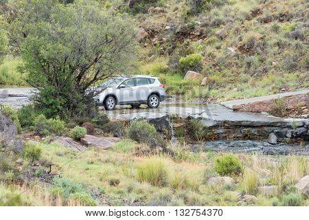 MOUNTAIN ZEBRA NATIONAL PARK SOUTH AFRICA - FEBRUARY 18 2016: A car crossing a stream on the Kranskop Loop in the Mountain Zebra National Park near Cradock