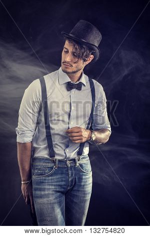 Portrait of brunette young man in glasses, bow-tie, suspenders and shirt looking at camera. Studio shot isolated on black background