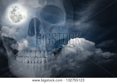 Halloween horror night background. Double exposure portrait of human skull combined sky with clouds . Full moon on right eye socket.