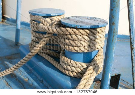 Naval weathered rope on blue painted metallic coils