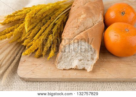 French Bread Baguettes On Bread Board And Mandarin Oranges