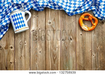 Rustic background for Oktoberfest with Bavarian white and blue fabric, beer stein and soft pretzel