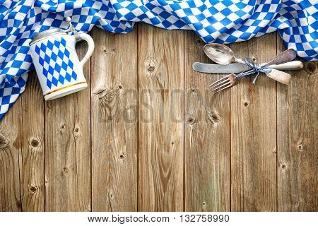 Rustic background for Oktoberfest with Bavarian white and blue fabric, beer stein and silverware