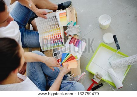Two persons choose color of a decor having inclined over catalogs. Objects for coloring of walls are on a gray concrete floor. People show each other examples of color of paint.