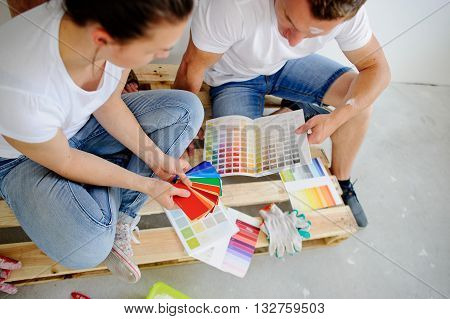 Man and woman choose color of decor sitting on a floor. They sit having inclined the heads over catalogs and pick the color of paint. The woman points to a sample which is pleasant to her.