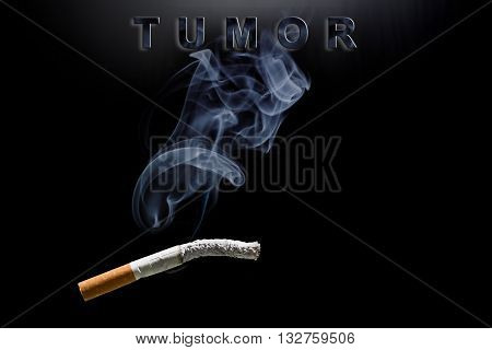 Burning cigarette, smoke and text tumor on black backstage