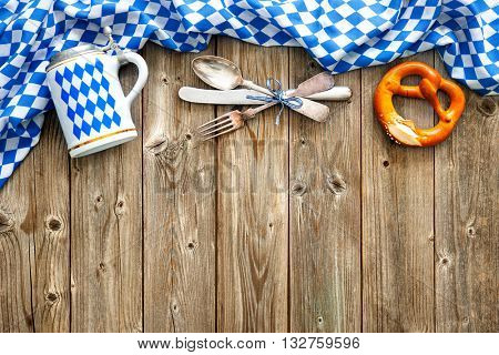 Rustic background for Oktoberfest with Bavarian white and blue fabric, beer stein, soft pretzel and silverware