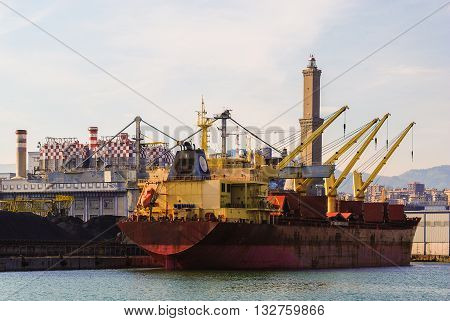 A freighter moored at one of the docks of the Genoa's harbor. The lighthouse in the background called