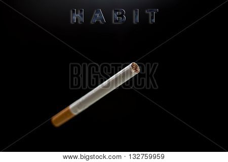 Only one cigarette and text habit on black background