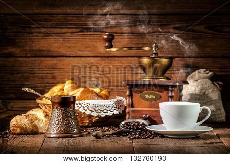 Coffee cup with croissants and coffee beans on wooden background