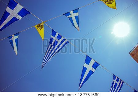 Triangular Greek Sea Flags On Blue Sky And Sun