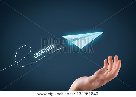Creativity improvement concept. Paper plane representing dreaming about creativity improvement and hand touching this dream comes true.