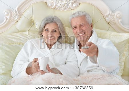 happy Senior couple reading in bed watching tv