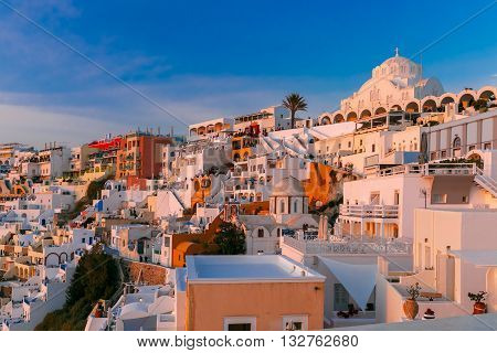Fira, main town of the island Santorini, sea, white houses and church at sunset, Greece
