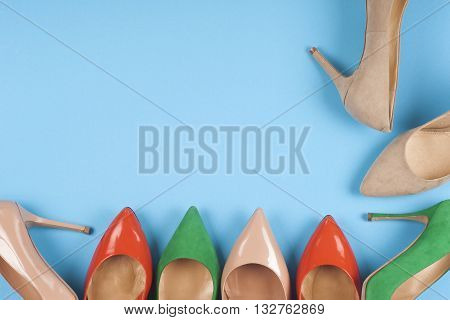A picture of different shoes Shot of several types of shoes Several designs of women shoes. Leather Shoe. Pile of various female shoes on on light blue background. Copy space for text.