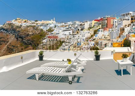 White sunbeds to relax on the veranda in Fira, modern capital of the Greek Aegean island, Santorini, Greece