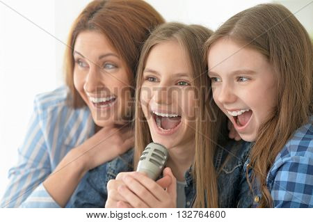 Portrait of happy mother and daughters singing karaoke