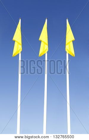 yellow flag  flying in the sky on high steel flagpole