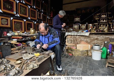 WUZHEN CHINA - MARCH 24: Unidentified chinese craftsman making traditional souvenirs on March 24 2016 in Wuzhen China. Wuzhen is a historic scenic town located in northern Zhejiang Province China