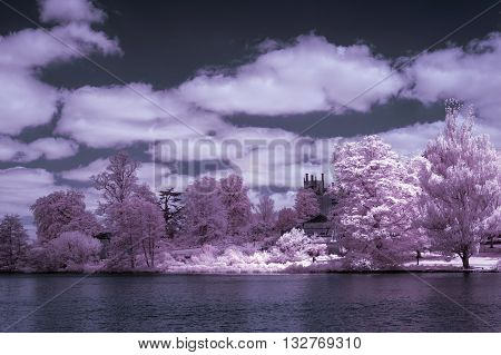 Stunning infra red alternative color landscape image of trees over river