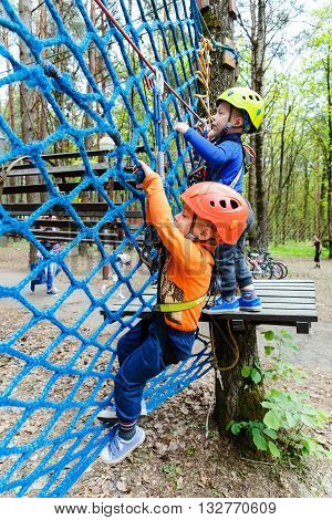Twin bothers climbing in adventure park is a place which can contain a wide variety of elements such as rope climbing exercises obstacle courses and zip-lines.