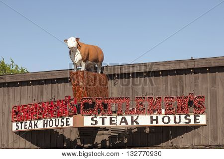 FORT WORTH USA - APR 6: Exterior of the Cattlemen's Steak House with a cow statue on top of the building. April 6 2016 in Fort Worth Stockyards Texas USA