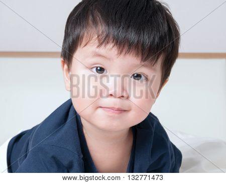 Asian boy toddler smiling blue shirt shot at close range.