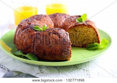 Zucchini bundt cake with orange glaze on plate