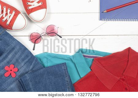 Women Clothing Set And Accessories On A Rustic Wooden Background. Sports T-shirt And Sneakers In Bri