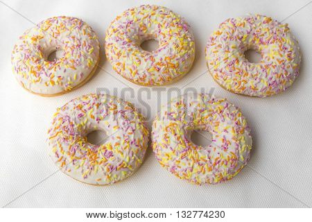 Donuts in the form of Olimpidy symbol: the five rings. Muffins  for tea. Tasty food cakes. Classic cakes: fried doughnuts glazed with caramel. Nutritious dish that promotes obesity.