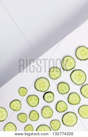 Sliced cucumbers on a white background with empty space above divided with shadow