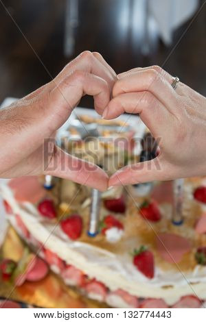 Bride and groom in front of the cake making a heart with hands