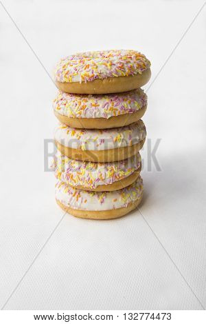 Doughnut are stacked in a column. Donuts for tea. Tasty food cakes. Delicious classic cakes: fried doughnuts glazed with caramel. Nutritious dish that promotes obesity.