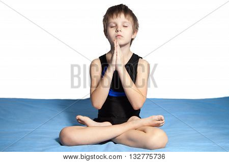 The young who is boy practices yoga