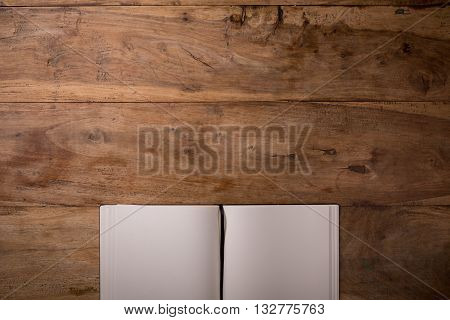 Book opened blank on dark wooden background with copyspace top-view closeup.