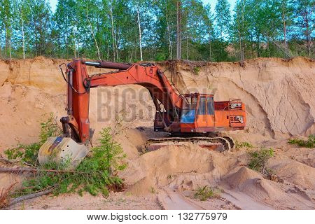 Excavator working on sand dunes in quarry