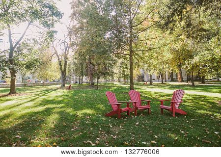 Three red chairs in the park at the college campus in small American town.