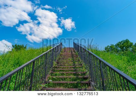 Stairway to heaven. Stairs among grass to blue sky.