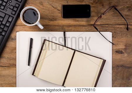 Wooden office desk with smartphone, glasses, notebooks and oher office supplies. View from above.