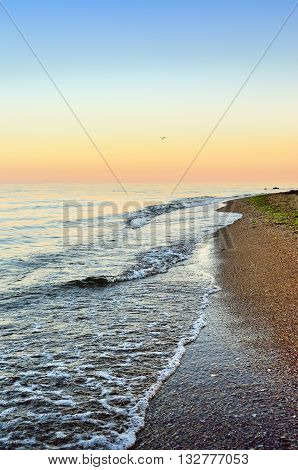 Sea Waves Wash The Beach Against  Backdrop Of Evening Sky