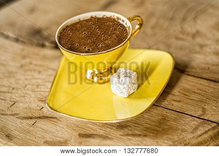 A cup of turkish coffee on the wooden table served with Turkish delight