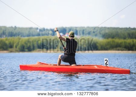 man athlete rower in a canoe rowing across lake during competition