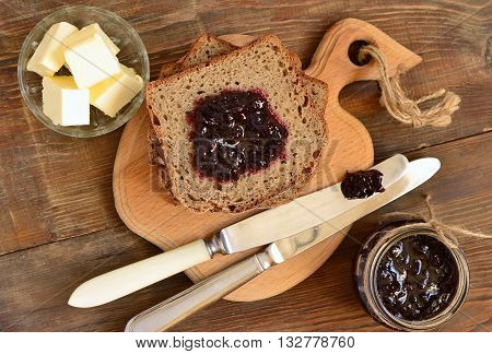 Wholegrain toast with blackcurrant jam and butter, top view