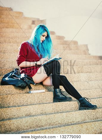 Pretty young blue-haired grunge girl sitting on stairs and reading a book